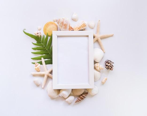 Bovenaanzicht, strand, schelp en witte fotolijst.