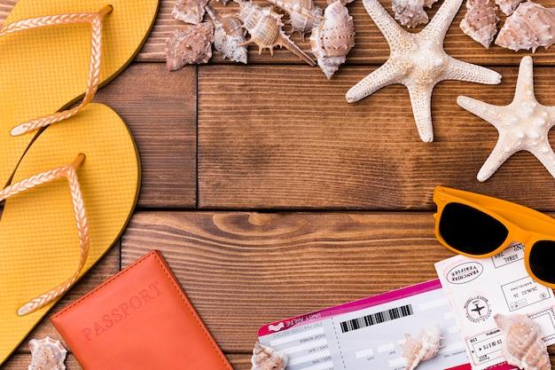Bovenaanzicht strand slippers en paspoort met zonnebril
