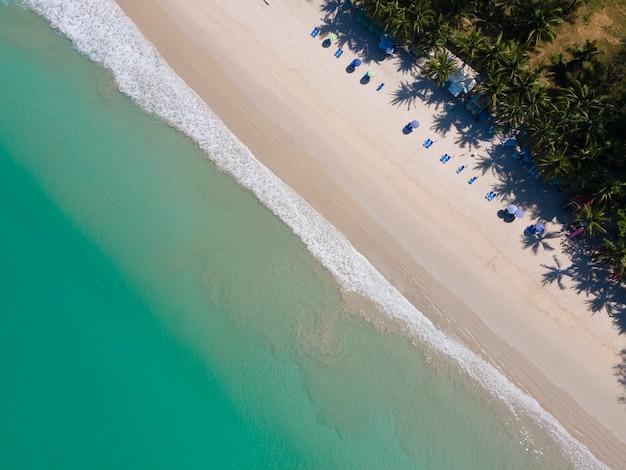 Bovenaanzicht strand zee in helder zeewater en strandzand. groene treen bij strand.