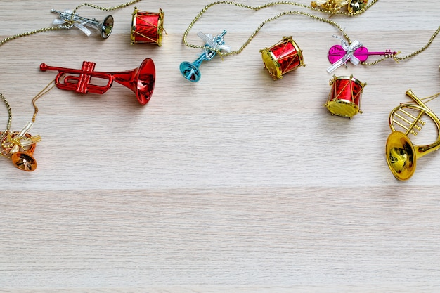 Bovenaanzicht studio shot van kleine kleurrijke glanzende mock-up opknoping decoratieve muziekinstrumenten gitaar viool drums trompet trombone op zilveren touw en gouden ketting op lichtbruine houten tafel met kopieerruimte.