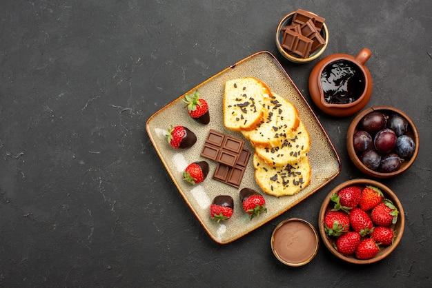 Bovenaanzicht stukjes cake smakelijke stukjes cake met chocolade en aardbeien en kommen met aardbeien, bessen en chocoladesaus aan de rechterkant van de tafel
