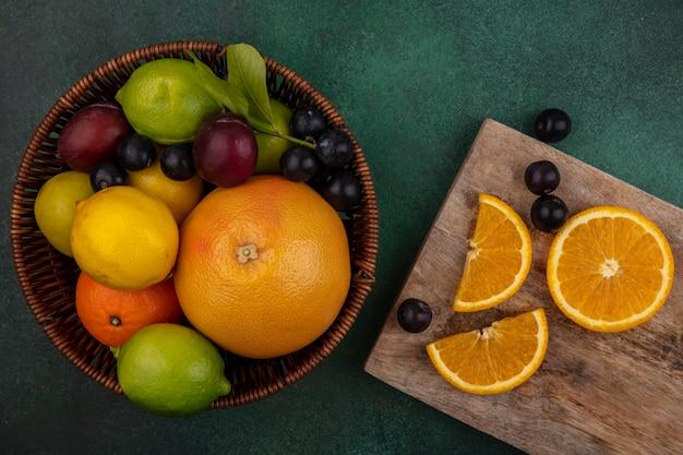 Bovenaanzicht stukjes sinaasappel op een snijplank met grapefruit kersen pruim citroen limoen en pruimen in een mand op een groene achtergrond