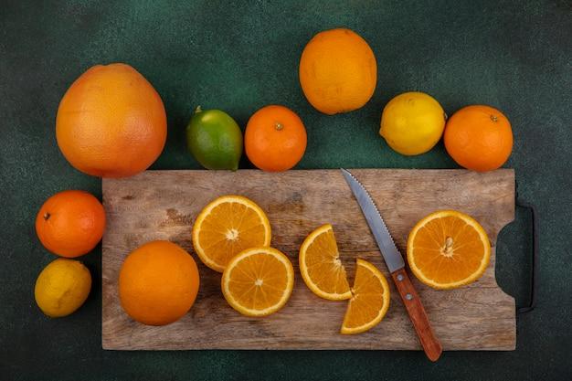 Bovenaanzicht stukjes sinaasappel op snijplank met mes citroen limoen en grapefruit op groene achtergrond