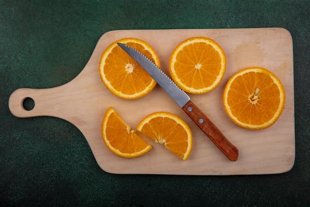 Bovenaanzicht stukjes sinaasappel op snijplank met mes op groene achtergrond