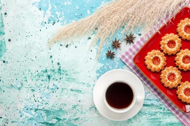 Bovenaanzicht suiker koekjes in rode plaat met kopje thee op de blauwe achtergrond