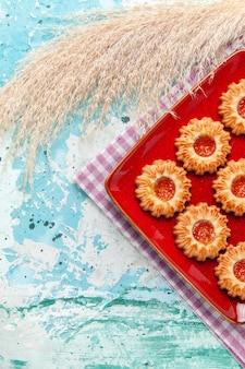 Bovenaanzicht suiker koekjes in rode plaat op blauwe achtergrond