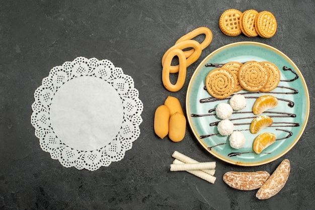 Bovenaanzicht suiker koekjes met koekjes en snoepjes op de grijze achtergrond