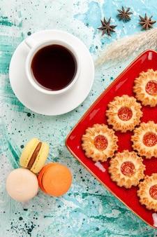 Bovenaanzicht suiker koekjes met kopje thee en macarons op de blauwe achtergrond