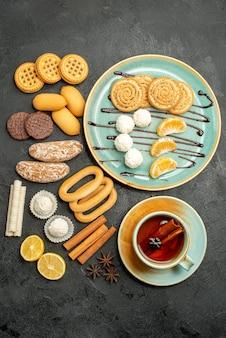 Bovenaanzicht suiker koekjes met snoepjes en kopje thee op grijze achtergrond