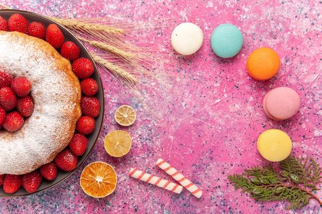 Bovenaanzicht suiker poedertaart aardbeientaart met macarons op de roze