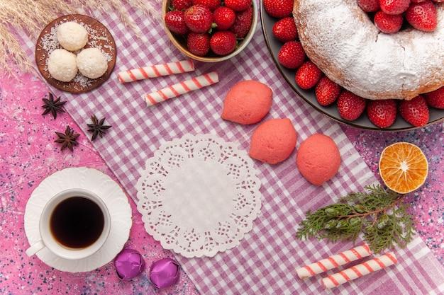 Bovenaanzicht suiker poedertaart aardbeientaart met roze taarten en thee op roze