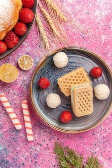 Bovenaanzicht suiker poedertaart aardbeientaart met wafels op lichtroze