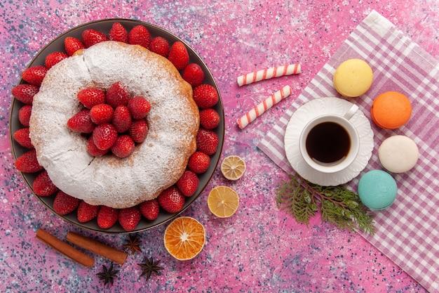 Bovenaanzicht suiker poedertaart met franse macarons en thee op roze