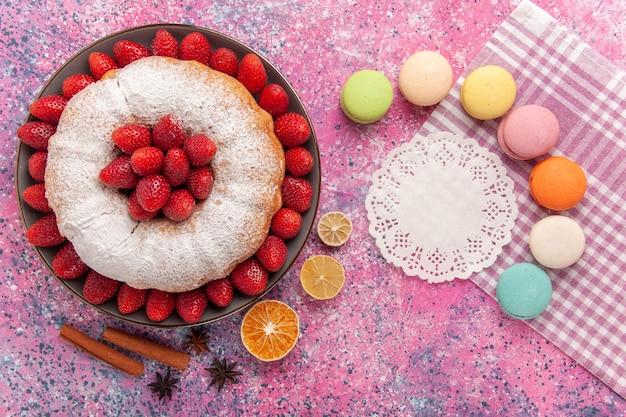 Bovenaanzicht suiker poedertaart met macarons op lichtroze