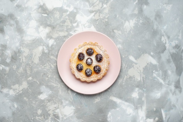 Bovenaanzicht suiker poedervormige cake met kersen bovenop op de lichte achtergrond taart taart zoete suiker bakken