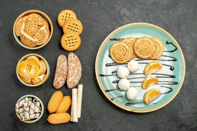 Bovenaanzicht suikerkoekjes met koekjes en snoepjes op donkergrijze achtergrond