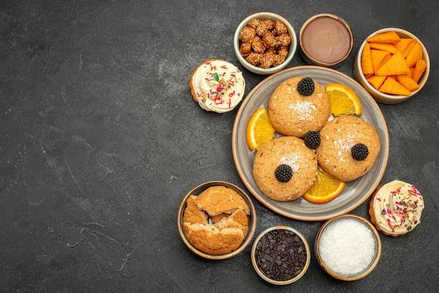 Bovenaanzicht suikerkoekjes met stukjes sinaasappel op donkere koekjeskoekjes, zoete theecake