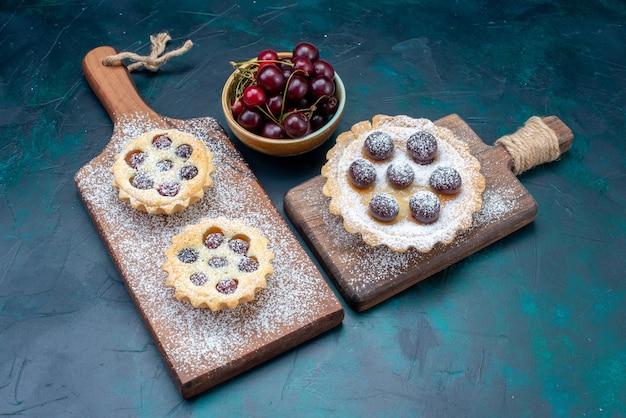 Bovenaanzicht suikerpoeder cakes met kersen erin en samen met verse zure kersen op de donkerblauwe tafel fruitcake zoet