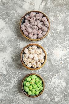 Bovenaanzicht suikersuikergoed in kleine bordjes op een wit bureau kandijsuiker bonbon thee zoet koekje