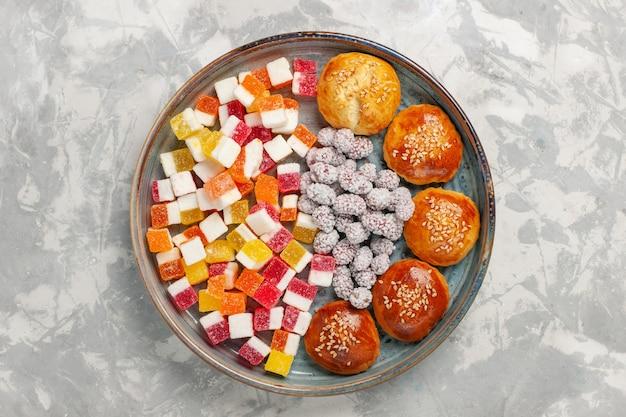 Bovenaanzicht suikersuikergoed met kleine broodjes op witte ondergrond