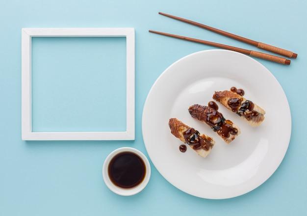 Bovenaanzicht sushi dag concept met sojasaus en eetstokjes