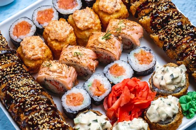 Bovenaanzicht sushi set hete sushi roll met teriyaki saus en sesamzaadjes philadelphia met zalm sake maki wasabi en gember op een bord