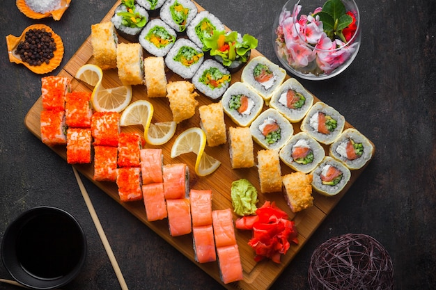 Bovenaanzicht sushi set met sojasaus en eetstokjes in houten serveerplank