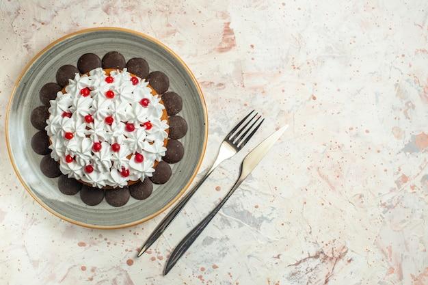 Bovenaanzicht taart met banketbakkersroom en chocoladevork en dinermes