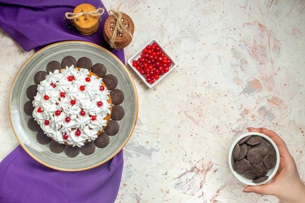 Bovenaanzicht taart met banketbakkersroom op plaat paarse sjaal cookies vastgebonden met touw bessen in kom chocolade kom in vrouwelijke hand op witte tafel