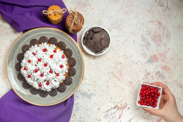 Bovenaanzicht taart met banketbakkersroom op plaat paarse sjaal cookies vastgebonden met touw chocolade in kom bessenkom in vrouwelijke hand op witte tafel