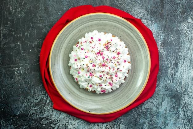 Bovenaanzicht taart met crème rode sjaal op grijze achtergrond