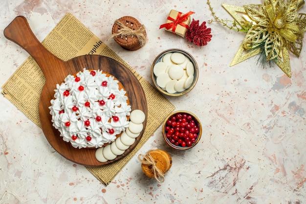 Bovenaanzicht taart met witte banketbakkersroom op houten bord op krant en en kerst ornamenten