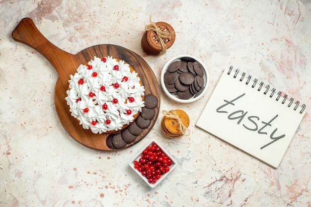 Bovenaanzicht taart met witte banketbakkersroom op snijplank kommen met bessen en chocolade koekjes vastgebonden met touw smakelijk geschreven op notitieboekje op lichtgrijze achtergrond