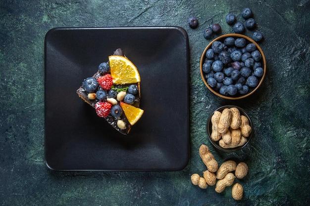 Bovenaanzicht taart plak heerlijke chocoladetaart met fruit in plaat op donker