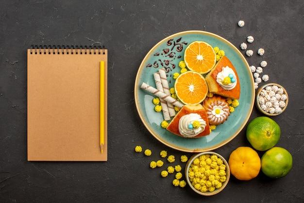 Bovenaanzicht taart plakjes met gesneden verse mandarijnen en snoepjes in het donker