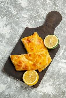 Bovenaanzicht taarten en citroenen taarten limoen en citroen op de donkere houten snijplank op de grijze achtergrond the
