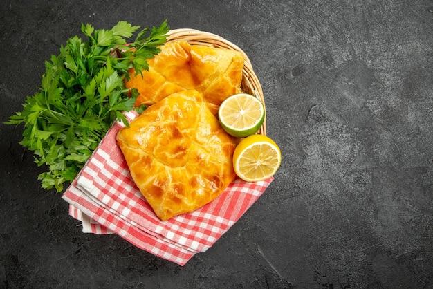 Bovenaanzicht taarten en kruiden twee taarten kruiden en citroenen naast het geruite tafelkleed in de houten mand