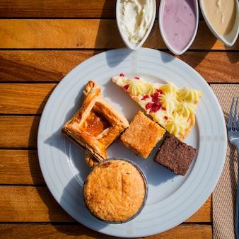 Bovenaanzicht taarten op een licht houten tafel