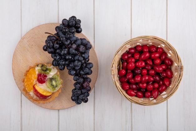 Bovenaanzicht taartje met zwarte druiven op een standaard met kornoelje in een mand op een witte achtergrond
