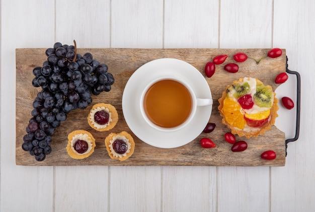 Bovenaanzicht taartjes met een kopje thee zwarte druiven en kornoelje op een snijplank