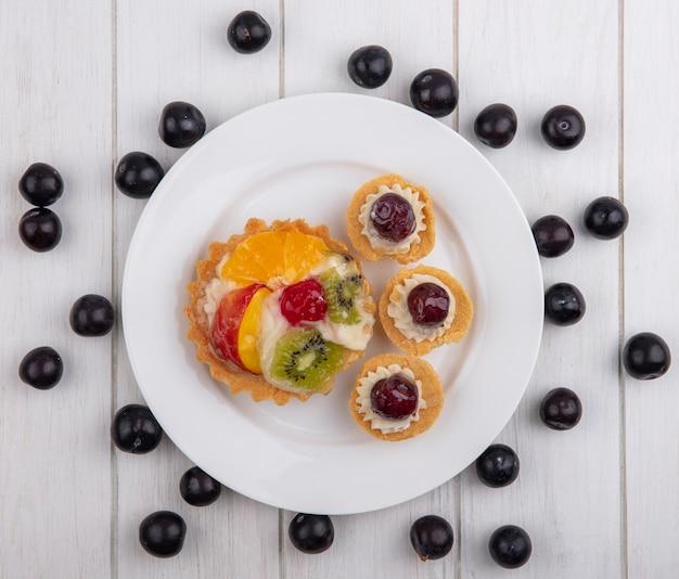 Bovenaanzicht taartjes met kersen kiwi en sinaasappel op een plaat met zoete kersen op een witte achtergrond
