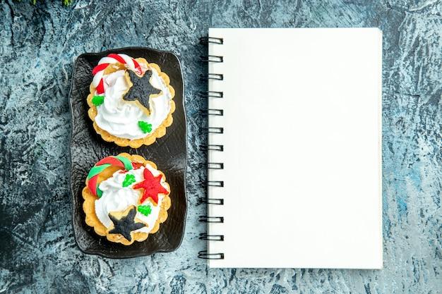 Bovenaanzicht taartjes op zwarte plaat notebook op grijze tafel