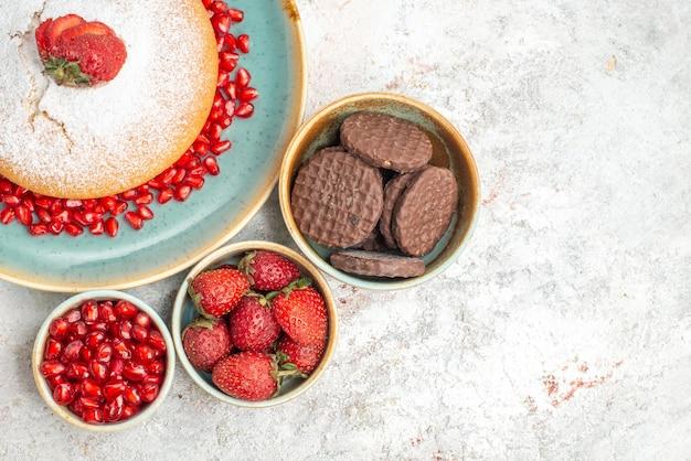 Bovenaanzicht taartkommen met koekjes verschillende soorten bessencake met aardbeien