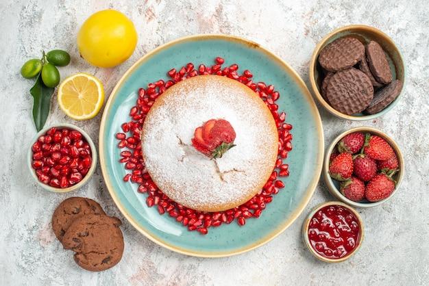 Bovenaanzicht taartkommen van chocoladekoekjes, bessen, citroen en cake met aardbeien