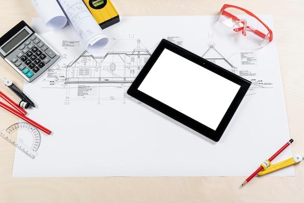 Bovenaanzicht tablet bovenop architecturaal plan