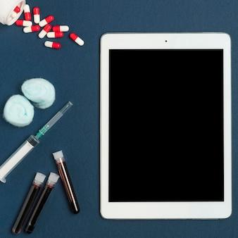 Bovenaanzicht tablet met medicijnen en spuit