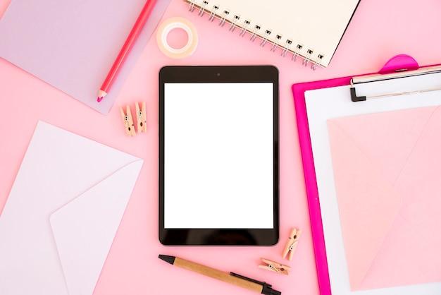 Bovenaanzicht tablet met roze briefpapier