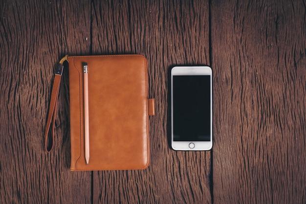 Bovenaanzicht tabletcomputer en telefoon op hout achtergrond