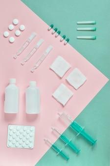 Bovenaanzicht tabletten, spuiten m verschillende medische op gekleurd karton, roze, blauw en lichtgroen. medicijnen op kleurkarton op een rij. bovenaanzicht. flatlay. indeling