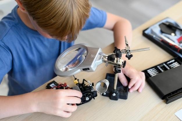 Bovenaanzicht tafel met uitvinder van het kind die een robot met radiobesturing assembleert